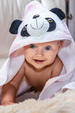 Cute baby in a towel crawling on the sofa royalty free stock photo