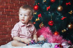 Cute baby with toys and Christmas tree on background. Holidays celebration concept. Christmas. Beautiful little baby boy celebrates Christmas, New Year`s Stock Images
