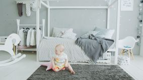 Cute baby trying to get up from floor at home stock footage