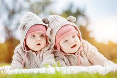 Cute baby twins lying together in a park wearing funny cozy sweaters. Stock Images