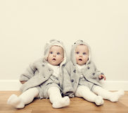 Cute baby twins sitting on wooden floor and wearing warm cozy sweaters. Vintage Stock Image
