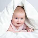 Cute baby under a blanket Stock Photos