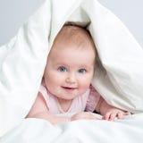 Cute baby under a blanket Stock Photos