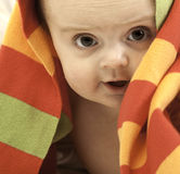 Cute baby under a colorful towel Stock Images