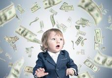 Cute baby under dollar rain Royalty Free Stock Photography
