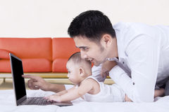 Cute baby using laptop with father Royalty Free Stock Images