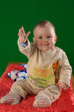 Cute baby waving hand in air. Cute baby sat on red blanket waving hand in air and smiling, green background Royalty Free Stock Photos