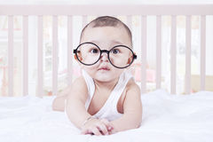 Cute baby wearing glasses in bedroom Royalty Free Stock Photography