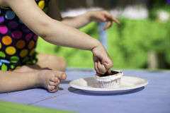Cute baby wearing spotted swimsuit tasting a cupcake with her finger Stock Image