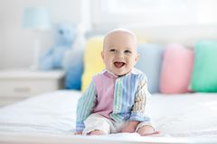 Cute baby on white bed stock photo