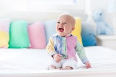Cute baby on white bed royalty free stock photo