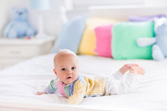 Cute baby on white bed Stock Image