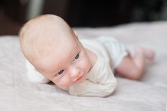 Cute baby on the white bed Royalty Free Stock Images
