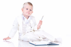 Cute baby in a white business suit with a diary Royalty Free Stock Image