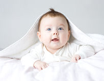 Cute baby in white clothing Stock Images