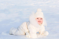 Cute baby in a white fur suit crawling in snow on a very sunny winter day stock image