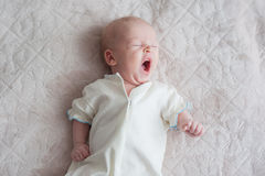 Cute baby yawns on a white background. Cute baby girl yawns on a white background Newborn on bed Stock Photo
