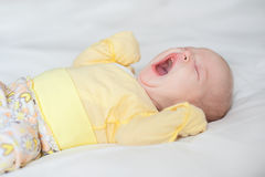 Cute baby yawns on a white background. Cute baby girl yawns on a white background Newborn on bed Royalty Free Stock Images