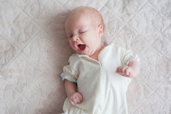 Cute baby yawns on a white background. Cute baby girl yawns on a white background Newborn on bed Stock Photos