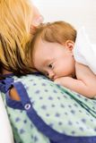 Cute Babygirl Lying On Mother In Hospital. Closeup of cute newborn babygirl lying on mother in hospital Stock Images