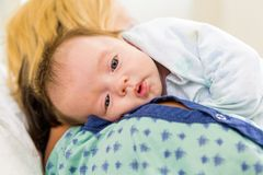 Cute Babygirl Resting On Mother's Shoulder In Royalty Free Stock Photo