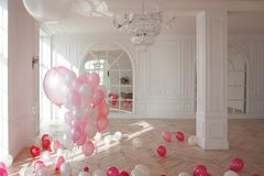 Cute background, the classic room with pink balloons, nobody. Luxurious living room with large window to the floor. The Palace is filled with pink balloons Royalty Free Stock Image