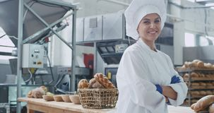 Cute baker woman in front of the camera looking straight and smiling large commercial kitchen , industrial machine on. The background stock video footage