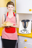 Cute baking woman holding fresh bread in kitchen. Cute baking woman holding fresh bread with bread making appliance in yellow kitchen Stock Photos