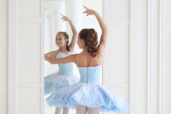 A cute ballerina in ballet costume and in pointe dances near the mirror. Girl in the dance class. The girl is studying ballet. Bal stock image