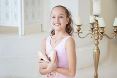 A cute ballerina in a ballet pink costume is sitting on the floor with pointe in her hands and smiling. Girl in the dance class. T. He girl is studying ballet royalty free stock photo