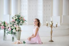 A cute ballerina in a ballet pink tutu and in poins sits on the floor. Girl in the dance class. The girl is studying ballet. Class. Ical ballet, dancing. Ballet stock photography