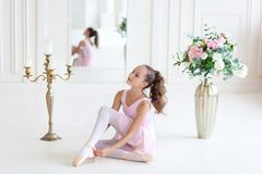 A cute  ballerina in a pink ballet costume is sitting on the floor and tying pointe shoes. Ballerina in the dance class.The girl i. S studying ballet. Ballerina royalty free stock photos