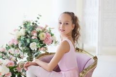 A cute ballerina in a pink tutu and in pointe sits in a chair. The girl is studying ballet. Ballerina dancing in a white studio. C royalty free stock image