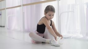 Cute ballet dancer tying ballet shoes before training