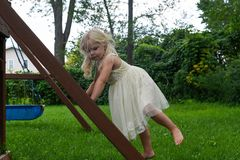 c999c13c952 Cute barefoot girl climbing swingset ladder. In dress up clothes stock  photos