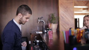 Cute Bartender preparing cocktail for an attractive girl. stock footage