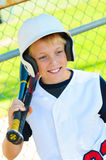 Cute baseball player in dugout Stock Photo