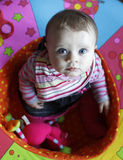 Cute bay girl playing (playpen). Overhead view of cute baby girl playing in soft ring shaped toy stock image