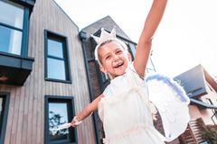 Cute beaming little girl feeling simply amazing while walking outside. Beaming girl. Cute beaming little girl feeling simply amazing and cheerful while walking royalty free stock images