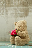 Cute bear doll holding rose bouquet Stock Photo