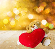Cute bear doll sit with red heart in dreamy gold bokeh light bac. Cute bear doll sit with red heart in dreamy golden bokeh light background Stock Photos