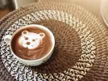 Cute bear face latte art Cocoa in white cup on paper box table royalty free stock photography