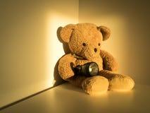 Cute bear holding flashlight sitting alone on wood floor at corner room. Stock Photo