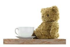 Cute bear sitting next to white hot coffee mug on wooden floor Royalty Free Stock Photography