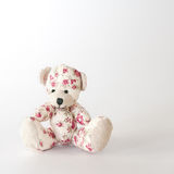 Cute bear-toy in pink flowers. On the white background Royalty Free Stock Photo
