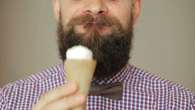 Cute Beard man in shirt with a bow tie eating ice cream. Cute Beard man in plaid shirt with a bow tie eating ice cream stock video footage
