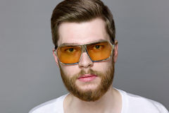 Cute bearded man in glasses from the sun studio portrait. Brutal sexy unshaven man with long beard and hendlebar moustache in sunglasses on gray background Stock Photo
