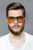 Cute bearded man in glasses from the sun studio portrait. Brutal sexy unshaven man with long beard and hendlebar moustache in sunglasses on gray background Stock Photos