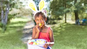 Cute African American girl eating and enjoying Easter candy wear stock photo