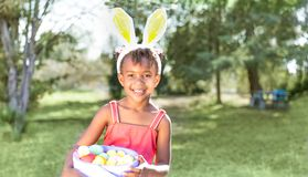 Cute African American girl wearing bunny ears, holding Easter ba royalty free stock images
